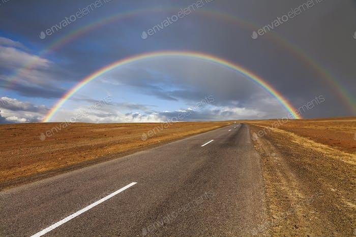Einsame Straße in der Wüste unter einem Regenbogen