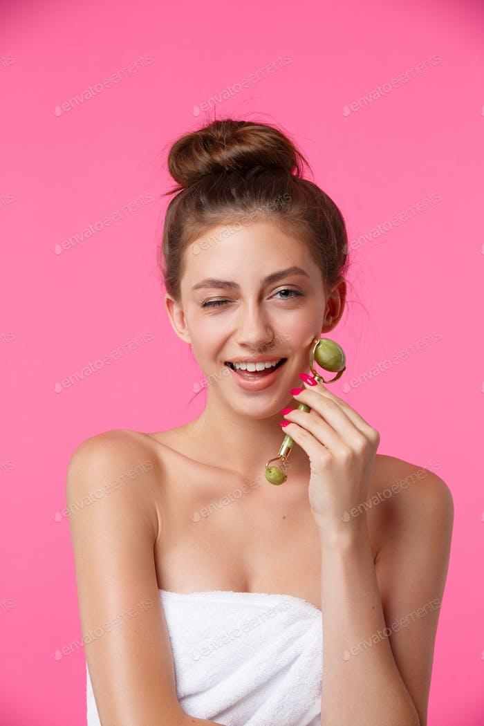 Woman applying jade roller for face massage