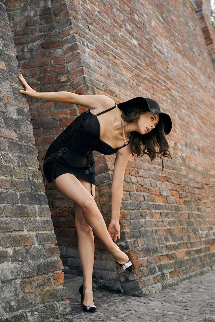 Frau in schwarzem Kleid posiert in der Nähe von Backsteinmauer
