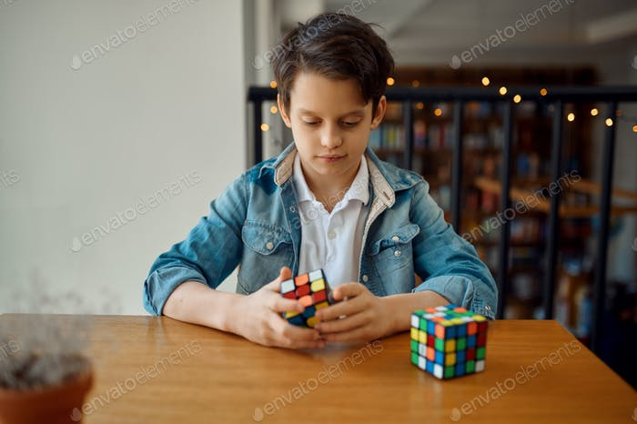 Boy trying to solve puzzle cube