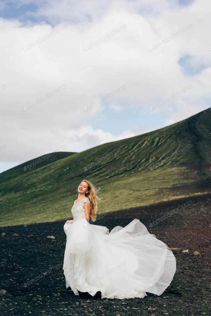 beautiful young bride in white wedding dress walking at majestic icelandic nature