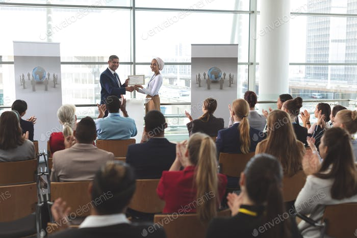 Businesswoman receiving award from businessman at business seminar in office building