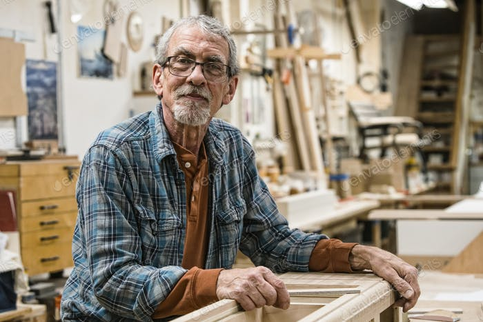 Portrait of a senior Caucasian carpenter in a large woodworking shoop.