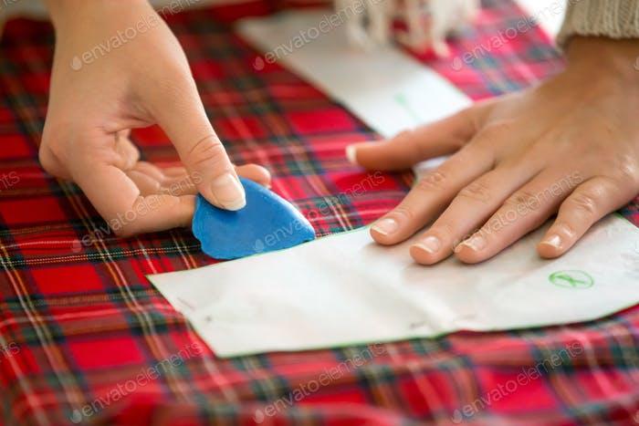 Hands working with a sewing pattern