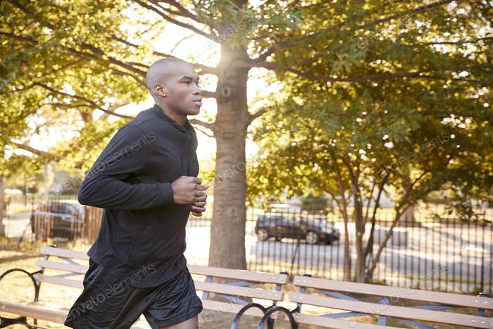 Young black man jogging in a Brooklyn park, close up