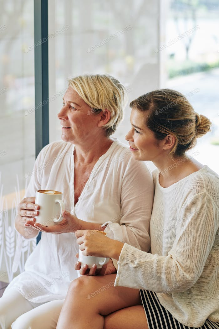 Mother and daughter with mugs of cappuccino