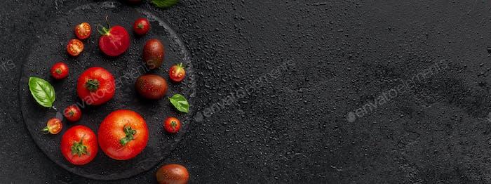 Saftige reife Kirschtomaten auf schwarzem Hintergrund