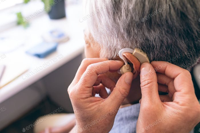 Male doctor applying hearing aid to senior woman ear in clinic at retirement home