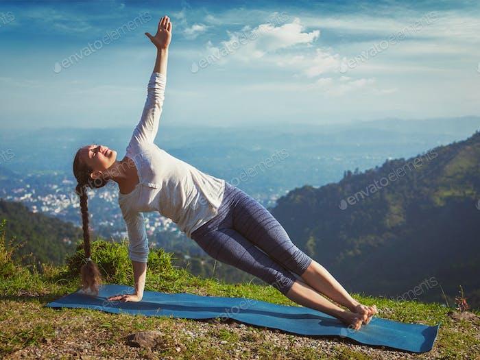 Woman doing yoga asana Vasisthasana - side plank pose outdoors