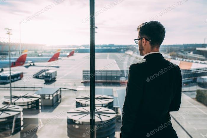 Zurück eines jungen Geschäftsmann stehend mit dem Koffer am Flughafen wartet auf den Flug