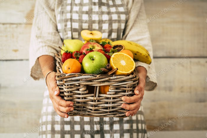 Fresh fruits bucket holded by adult woman