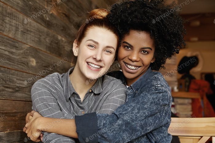Sweet tender indoor shot of happy interracial homosexual couple hugging and cuddling at cafe: Africa