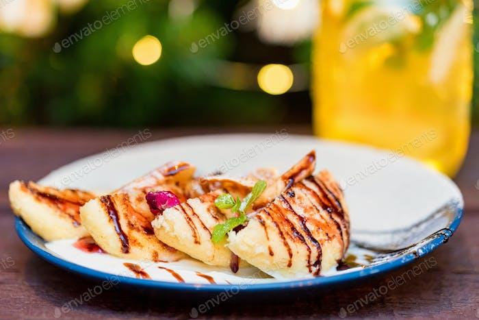 Hüttenkäse Pfannkuchen oder Syrniki mit Sahne, Fruchtmarmelade und Blumendekoration
