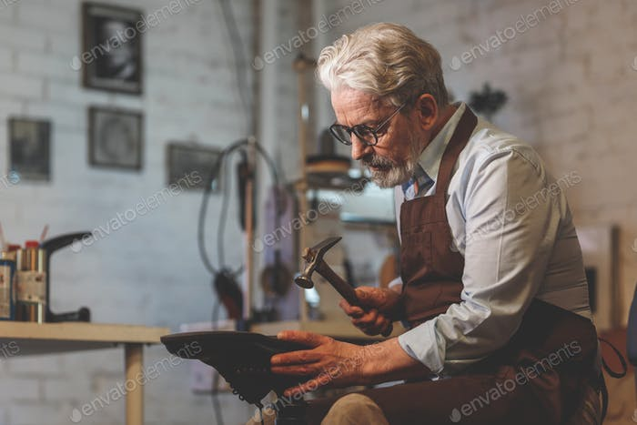 An elderly shoemaker in a workshop