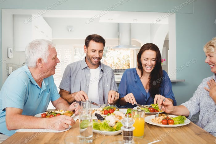 Family laughing while sitting at dining table with food in home