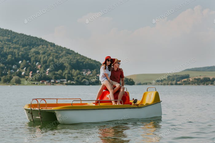 Portrait of smiling couple in love having fun pedal boating on hot summer day.