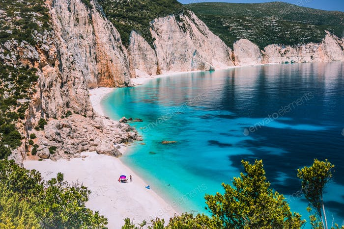 Amazing Fteri beach lagoon, Kefalonia, Greece. Tourists under umbrella chill relax near clear blue