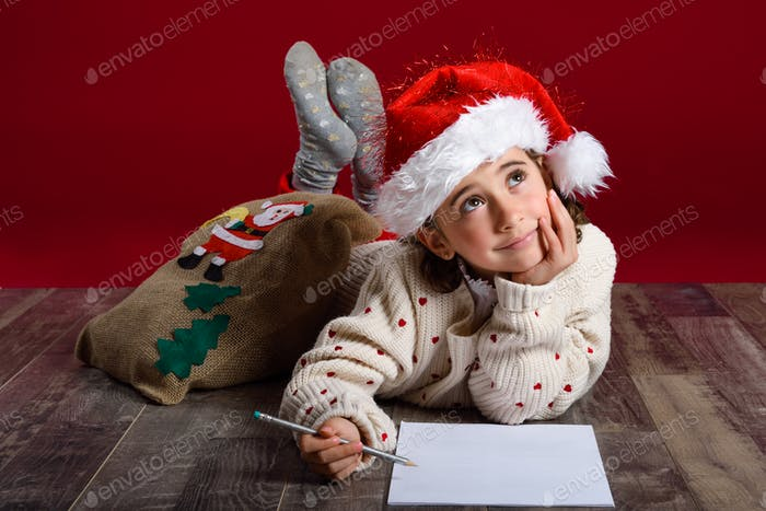 Adorable little girl wearing santa hat writing Santa letter