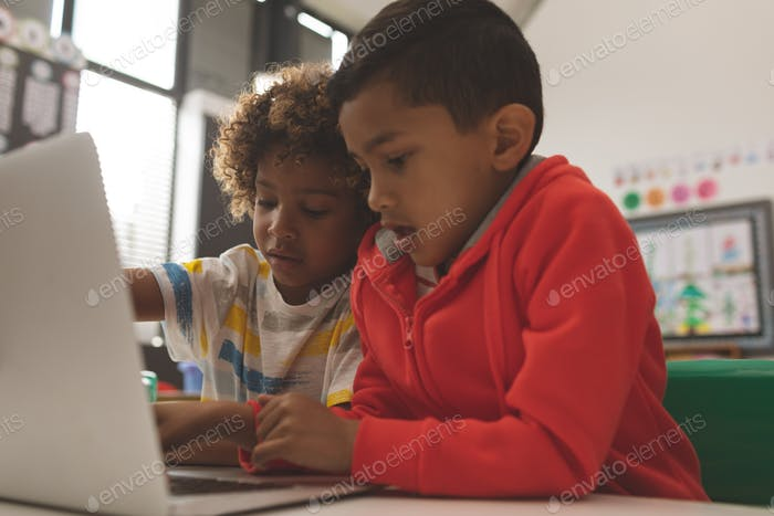 Close-up of two handsome school boys working on one laptop in classroom