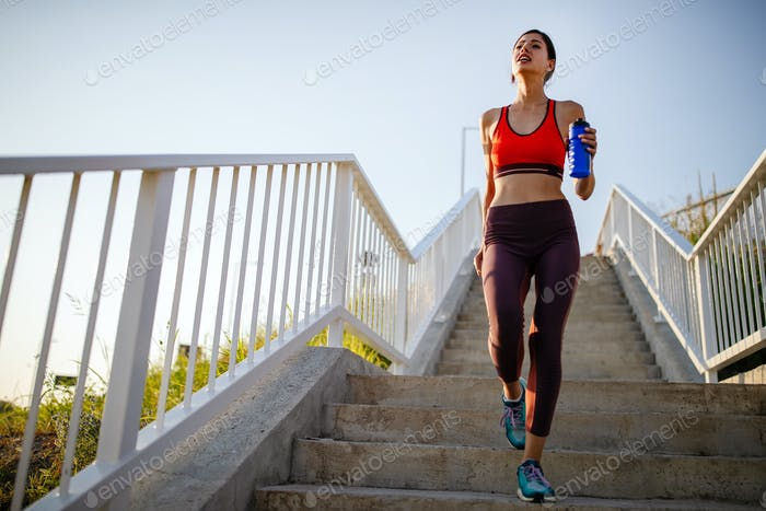 Portrait of fit cheerful woman resting after a run in a city