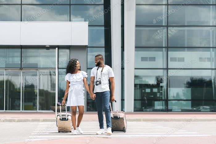 Black couple going out of airport building with luggage