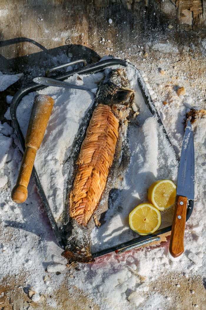 cooking Fish under the salt Crust. Summer lunch. healthy food rustic style.