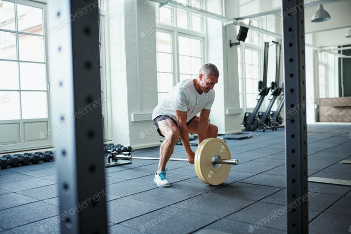 Senior man in sportswear lifting weights alone in a gym