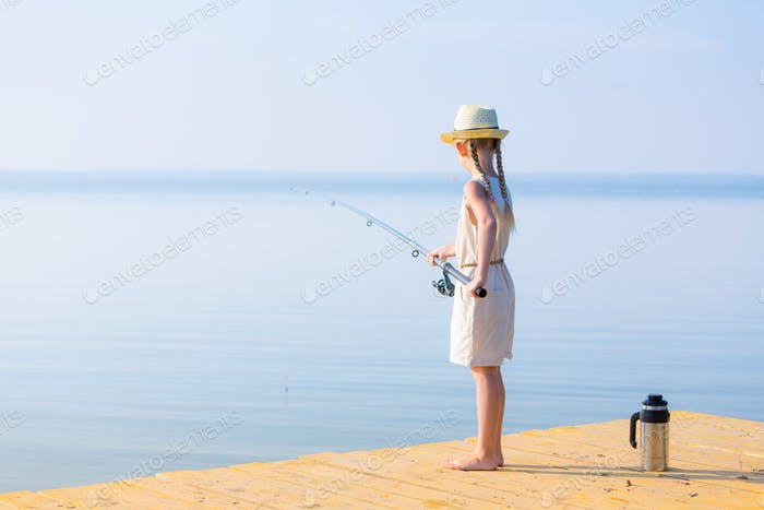 Girl in a dress and a hat with a fishing rod