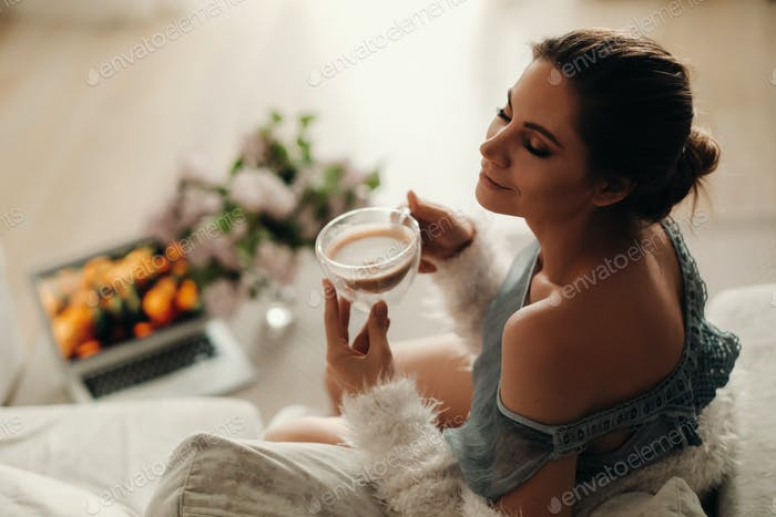 a relaxed girl at home drinks coffee and watches a movie.Domestic calm.The girl is sitting