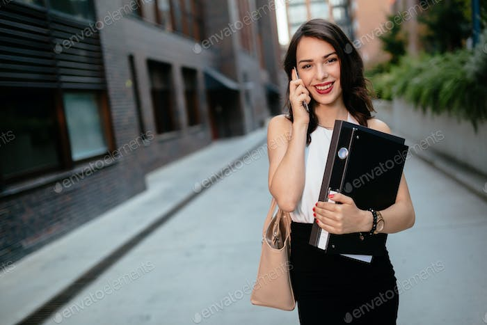 Beautiful businesswoman carrying folders
