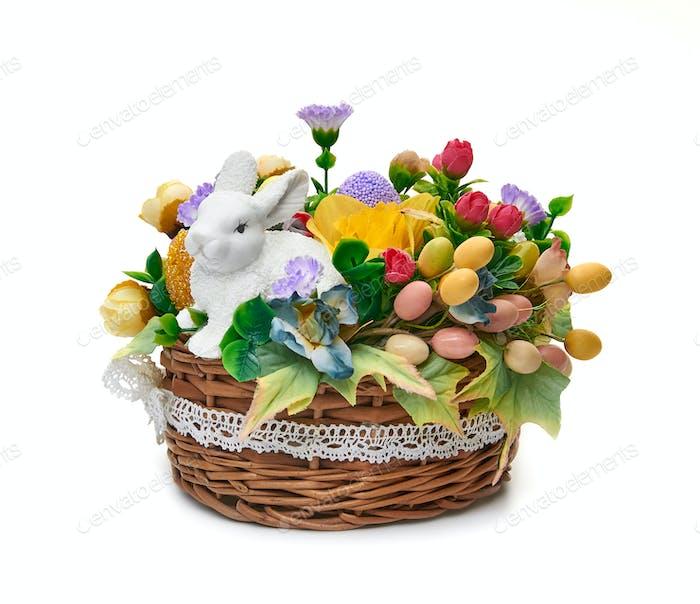 Osterkorb aus einem Blumenarrangement und einem Hasen auf weißem Hintergrund