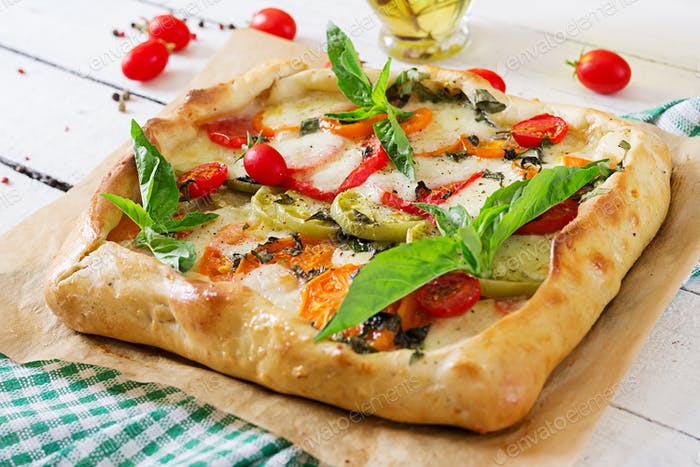 Mozzarella, tomatoes, basil savory pie on a white wooden background