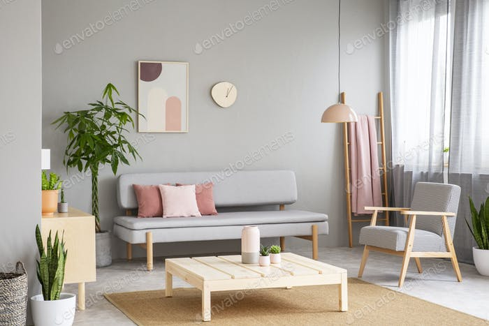Wooden table on carpet and armchair in grey flat interior with p