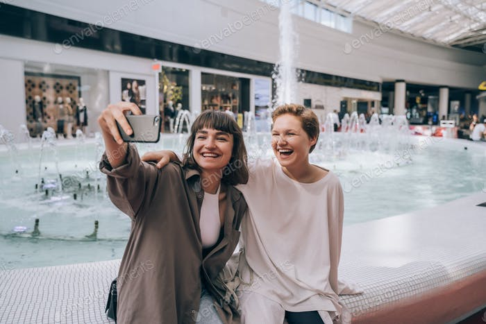 Two girls take a selfie in the mall, a fountain in the background