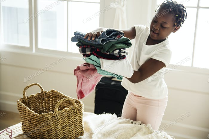 Young teen girl helping with folding the clothes