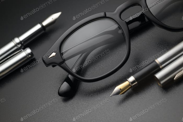 Black plastic eye glasses with two fountain pens on dark background
