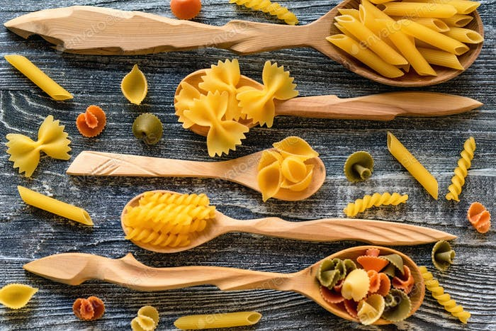Various mix of pasta on wooden rustic background