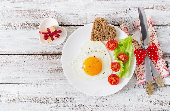 Fried eggs and bread in the shape of a heart and fresh vegetables.