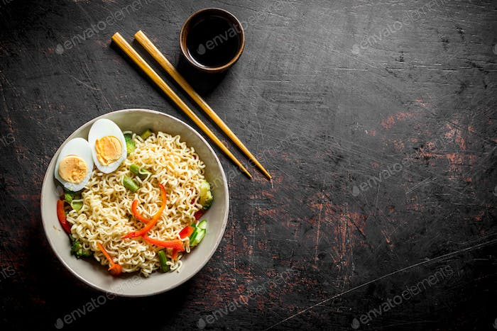 Instant noodles with vegetables and a sliced egg.