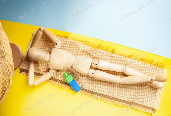 Wooden dummy on yellow as sand beach and blue as water.
