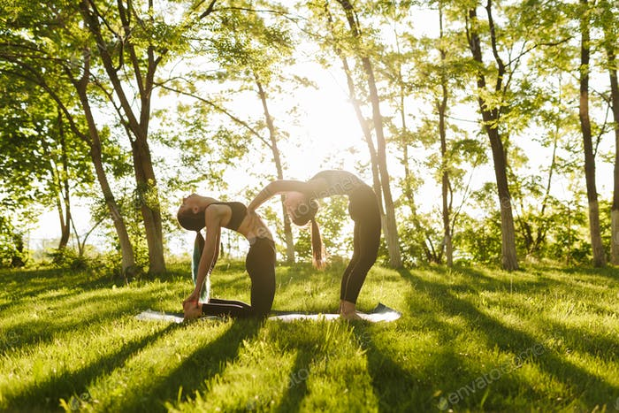 Photo of two ladies standing and  training yoga poses together outdoors