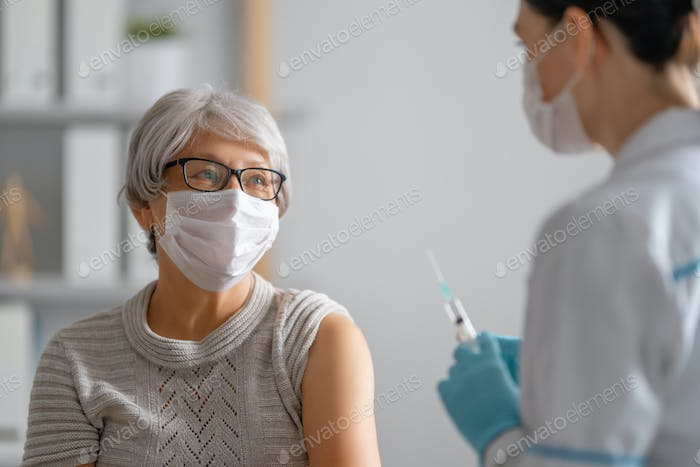 Doctor giving a senior woman vaccination