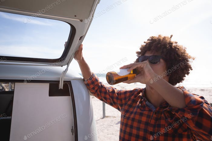 Front view of a Mixed-race man drinking a beer while he is closing car trunk of his camper van