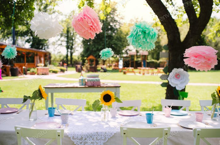 A table set for kids birthday party outdoors in garden in summer