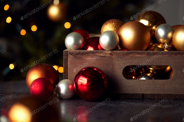 Wooden Box Of Christmas Tree Baubles With Tree Lights In Background