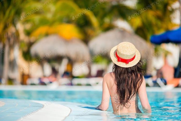 Beautiful young woman relaxing in outdoors pool