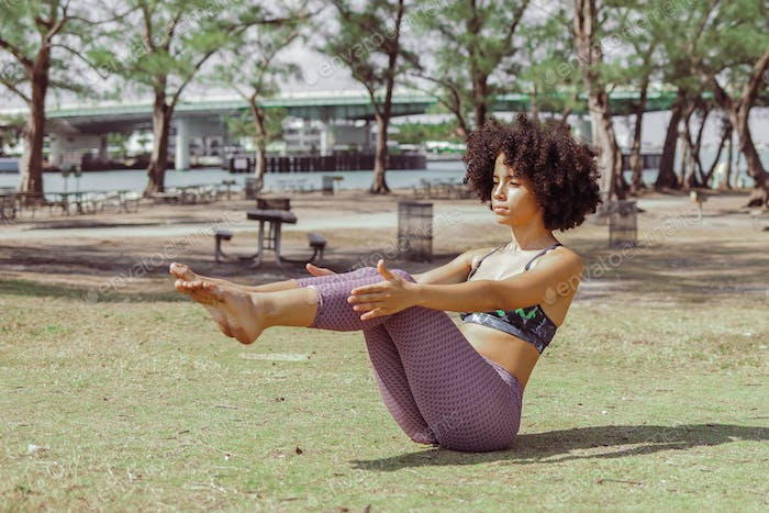 Girl practicing abdomen muscles on meadow