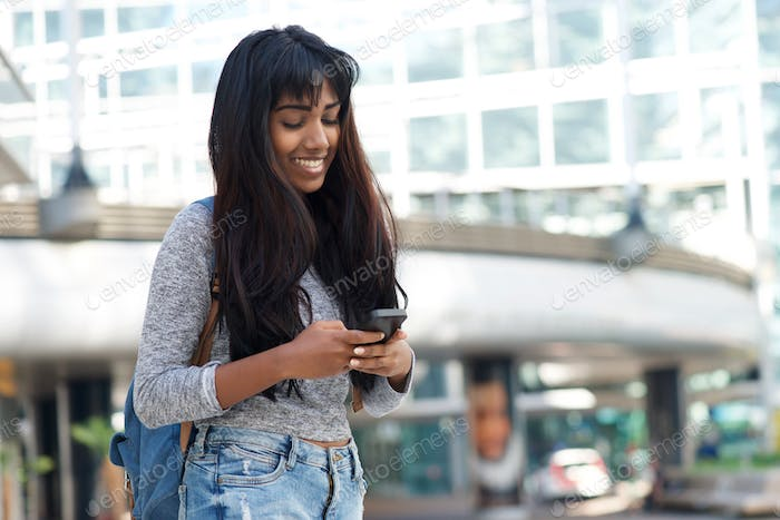 smiling young woman in the city with bag and looking at cellphone