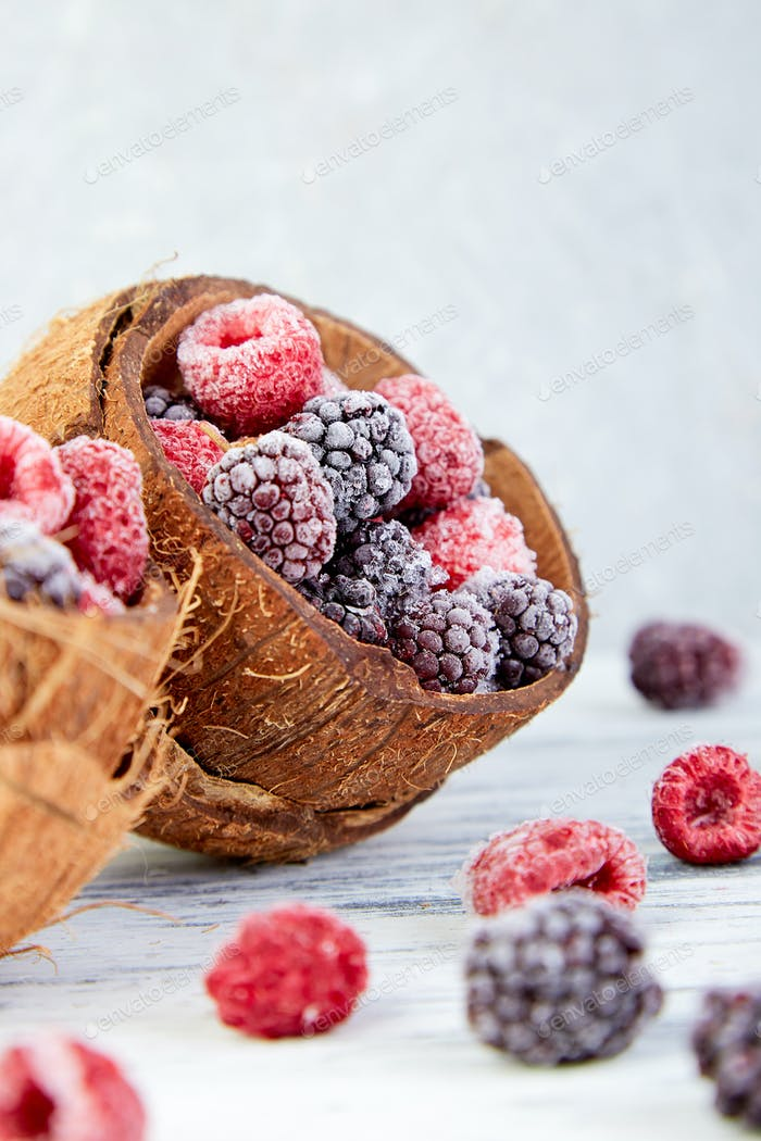 Frozen black and red raspberries in coconut bowl.