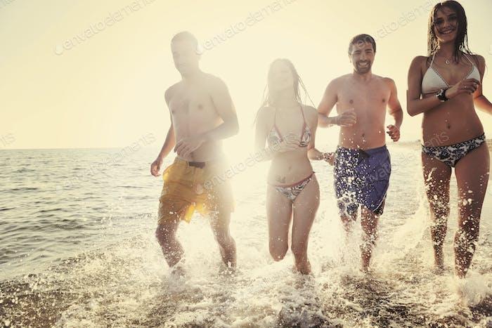 fröhliche Leute Gruppe haben Spaß und Laufen am Strand